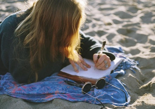 Girl journaling on sand