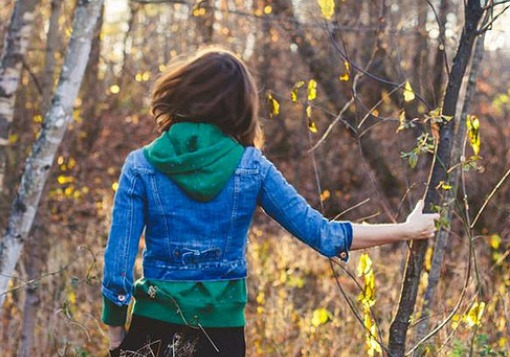 Girl with arm gripping tree